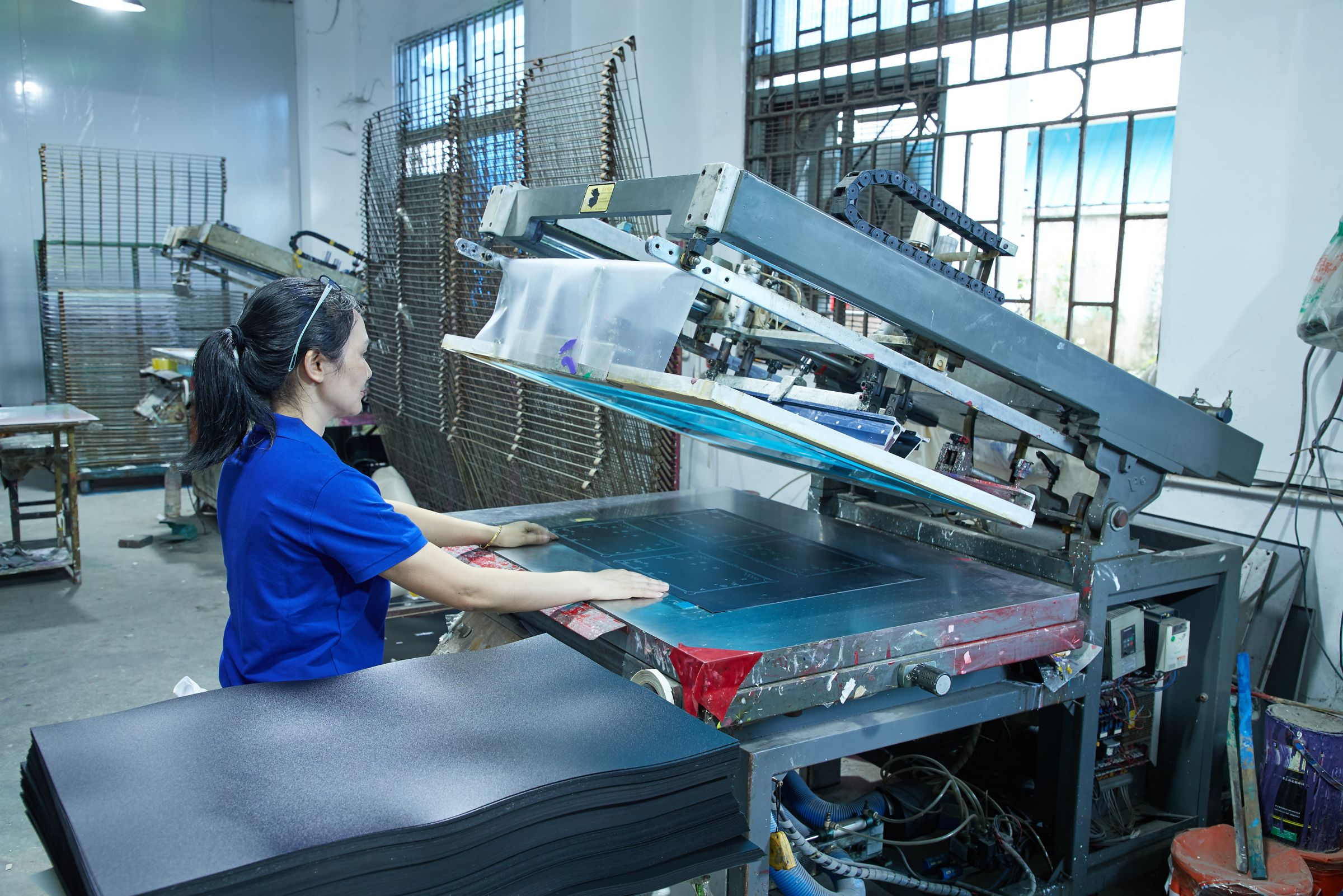 Silk screen printing machine for printing patterns on PP sheets.