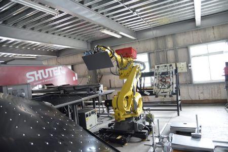 펀칭기에 원료를 공급하는 로봇.
