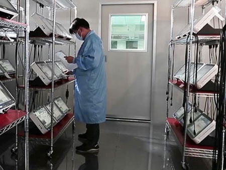 A QC engineer examine the products in the Burn-In Room.